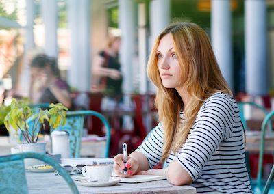 Frau im cafe schreibt in ein Tagebuch